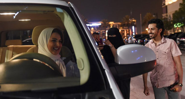 A Saudi woman films and shows support to Samar Almogren (L) who drives her car through the streets o
