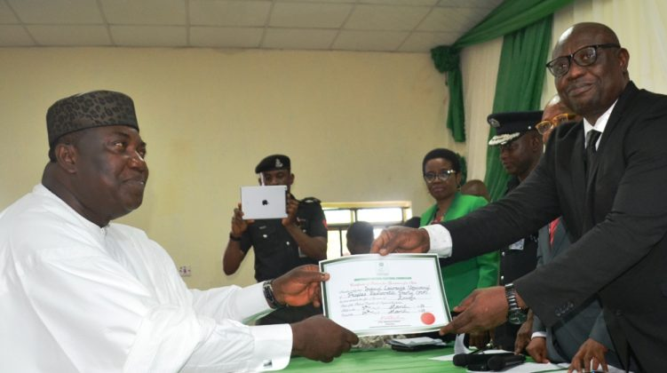 Gov Ugwuanyi (left) receiving the certificate from Okoye